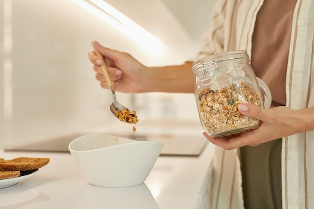 Современная женщина делает здоровый завтрак из мюсли, стоя в интерьере кухни