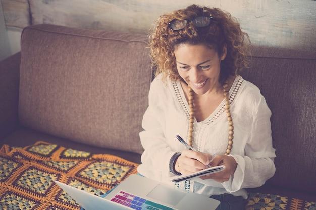 Современная женщина-менеджер-фрилансер работает дома с интернет-компьютером, ноутбуком с цветной клавиатурой, бумагой и ручкой для заметок - концепция счастья работать дома