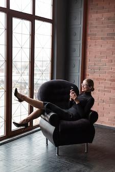 Современная женщина на диване с помощью мобильного телефона