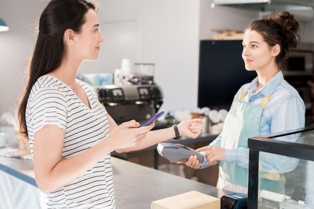 Modern woman paying by smart watch