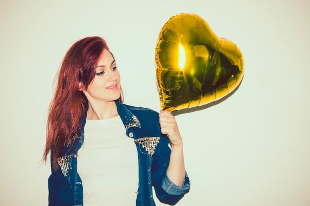 Современная женщина позирует с золотой шар