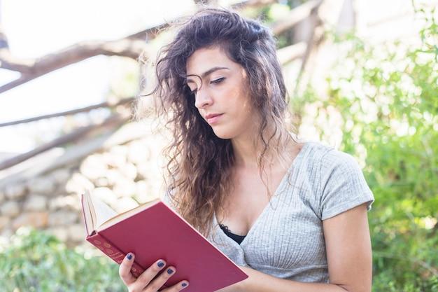 Современная женщина, читающая книгу в парке