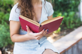 Modern woman reading a book in the park