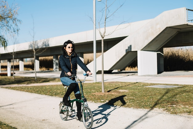 Modern woman riding bike in city