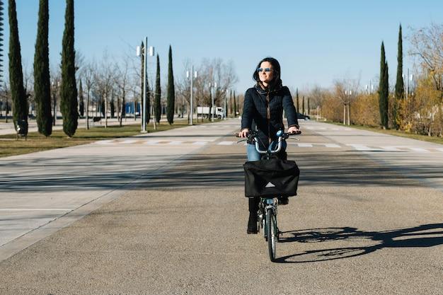 Modern woman riding bike in city