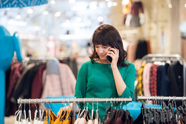 Современная женщина покупает одежду и разговаривает по телефону одновременно.
