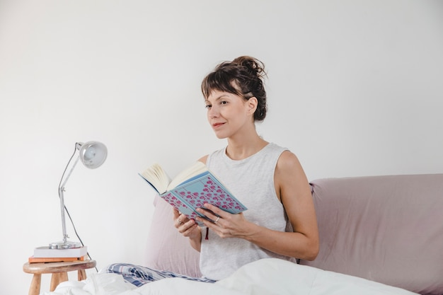 Modern woman sitting in bed reading