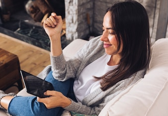 Modern woman sitting on the sofa using a tablet