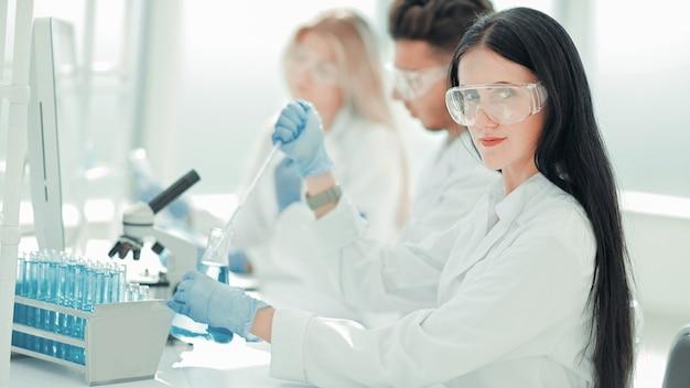 研究室のテーブルで同僚と一緒に座っている現代の女性