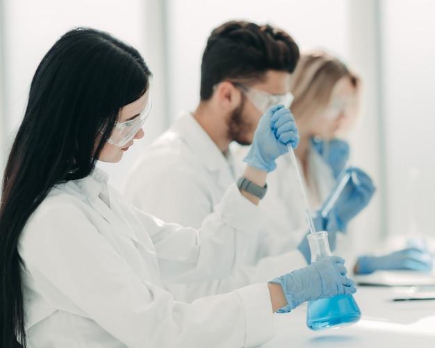 Современная женщина сидит с коллегами за лабораторным столом