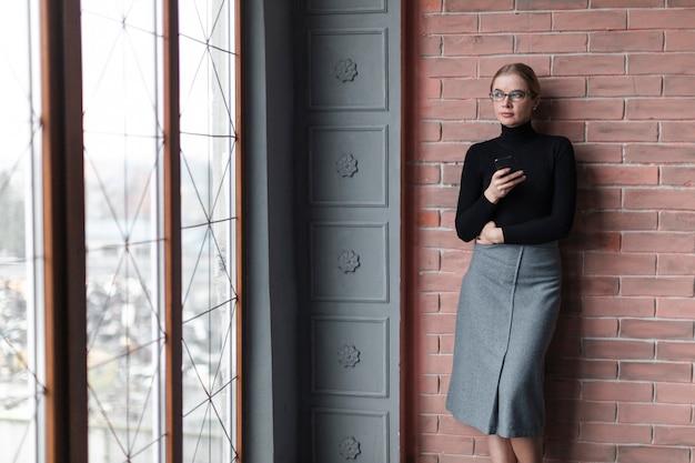 壁の隣に立っている現代の女性