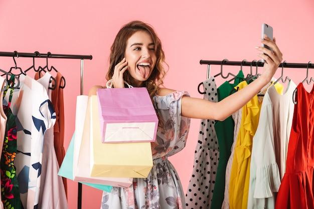 Современная женщина делает селфи на смартфоне в магазине возле вешалки с красочными сумками, изолированными на розовом