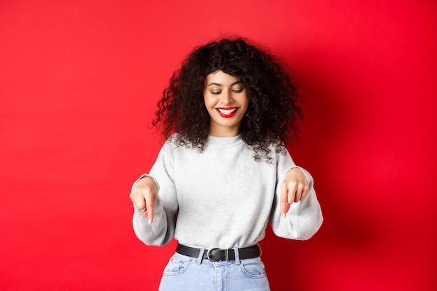 Современная женщина с кудрявой прической и красными губами, указывая пальцами вниз и улыбаясь счастливой, показывает рекламу ...