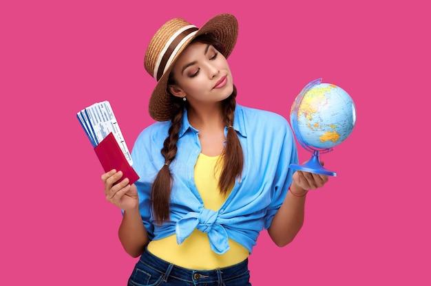 Современная женщина с маленьким глобусом и авиационными билетами внутри паспорта на розовом изолированном фоне. студентка в повседневной одежде и соломенной шляпе