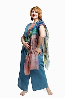 Modern woman with red hair in denim overalls barefoot. beautiful and happy aging. . full height. vertical.