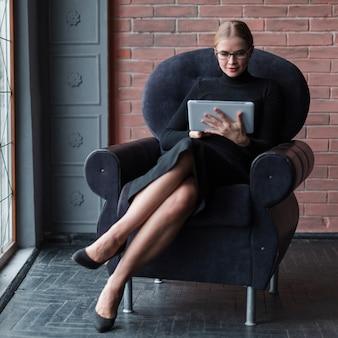 ソファの上のタブレットで現代の女性