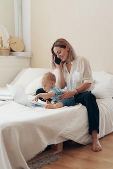 子供と働く現代の女性。マルチタスク、フリーランス、母性のコンセプト