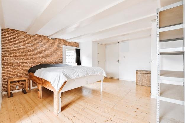 벽돌 벽과 금속 선반 선반이있는 넓은 조명 침실에 흰색 이불이있는 현대적인 목재 침대