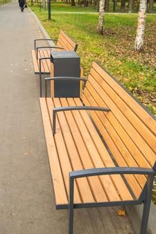 秋の公園のモダンな木製のベンチと壷、縦の写真。