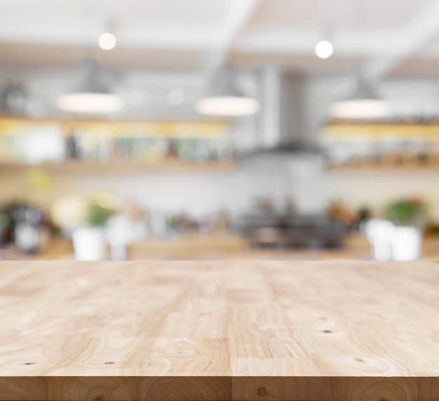 ぼやけたキッチンの背景の前にあるモダンな木の板の空のテーブル。製品の展示やモンタージュに使用されるパースペクティブテーブルトップ