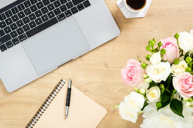 Modern wooden office desk table with laptop computer, bouquet of flowers, cup of coffee, paper notepad, pen.