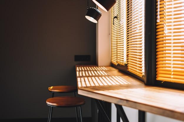 カーテン付きの大きな窓の近くのキッチンのモダンな木製テーブル