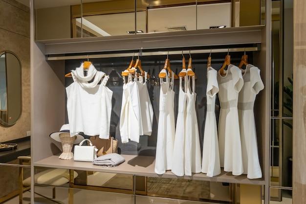 Современный деревянный шкаф с одеждой, висящей на рельсах, в дизайне интерьера гардеробной