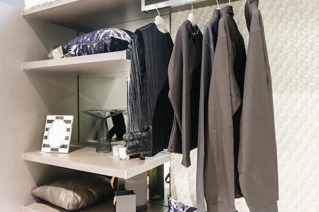 クローゼットデザインインテリアで歩くレールに掛けられた服を使った現代の木製ワードローブ