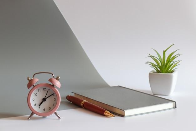 알람 시계 노트북 펜과 식물 모닝 컨셉이 있는 현대적인 작업장