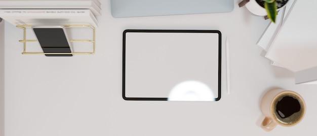 モダンなワークスペースの空の画面のタブレットは、コーヒーカップの携帯電話と白い机の上の装飾でモックアップ