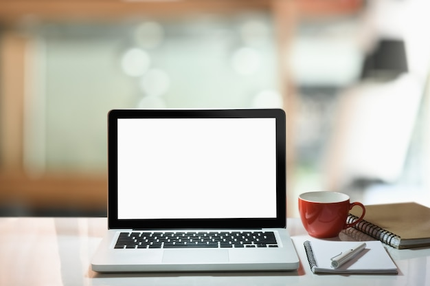 Modern work space, laptop with white screen, coffee cup and note book on white table.