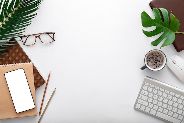 컴퓨터 키보드와 사무용품이 있는 현대적인 작업 공간. 열대 야자수 잎이 있는 흰색 탁자에 빈 휴대폰 모형. 프레임 플랫 레이.