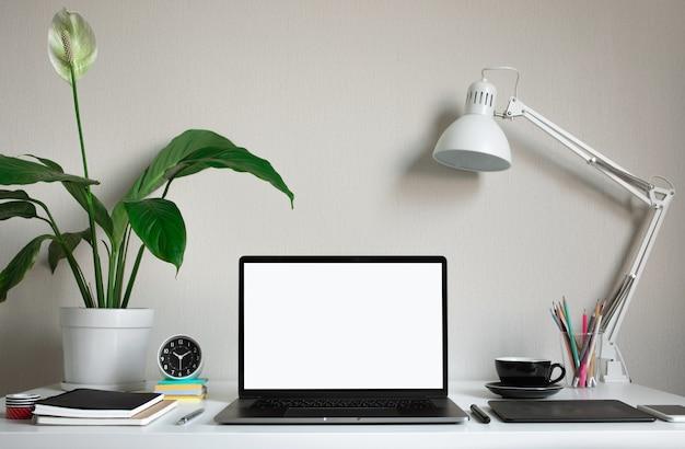 Современный рабочий стол с пустым компьютерным ноутбуком и аксессуарами в студии домашнего офиса