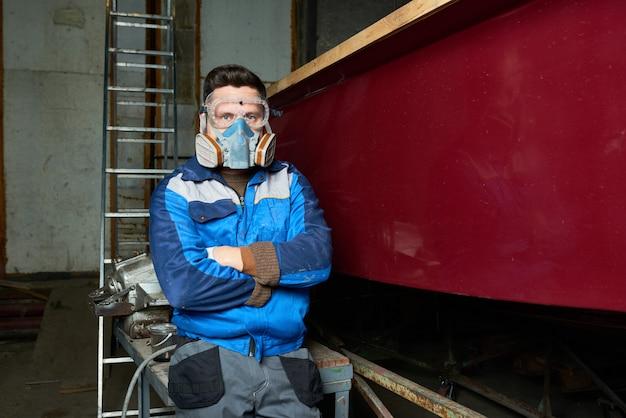 Современный рабочий в лодочной мастерской