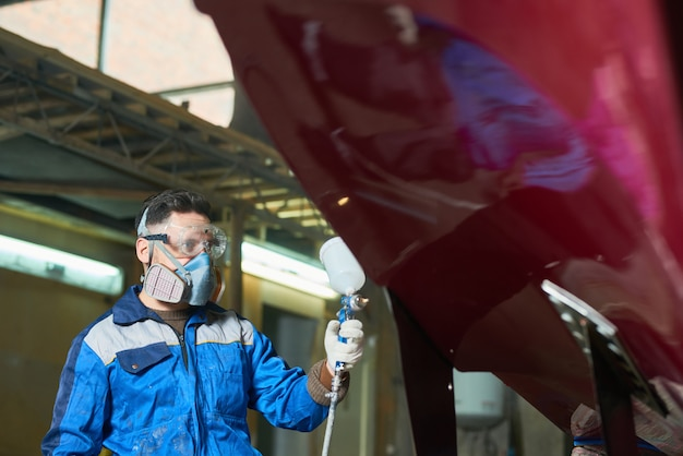 Modern worker painting boat in workshop