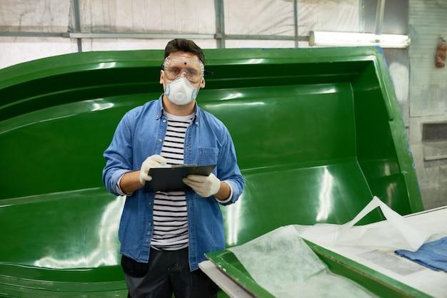 Современный работник позирует в мастерской по изготовлению лодок