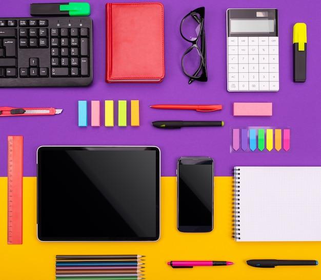タブレット、電卓、ノートブック、紫色とオレンジ色の背景にスマートフォンを持つ近代的な職場。事業コンセプト