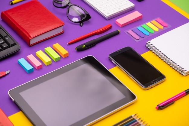 タブレット、電卓、ノートブック、スマートフォンを備えたモダンな職場