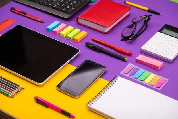 Modern working place with tablet, calculator, notebook and smartphone on purple and orange.
