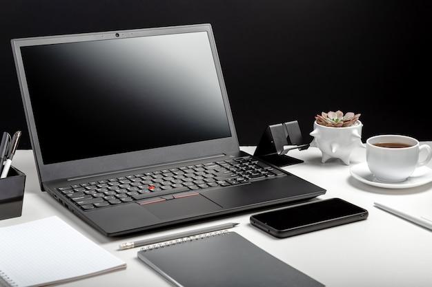 현대 직장 홈 오피스 노트북 화면 빈 디스플레이 작업 영역. 노트북 Pc 스마트 폰, 사무실 공급 업체, 커피 컵 식물 꽃이있는 데스크탑. 작업 책상 테이블 검은 배경. 프리미엄 사진