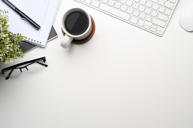 Современное рабочее место с кофейной чашкой, ноутбуком, очками и клавиатурой на белом столе.