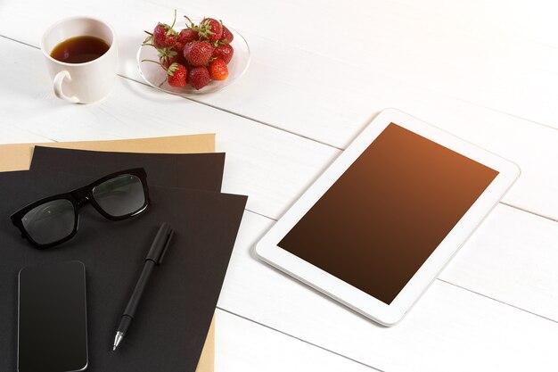 Современное рабочее место с цифровым планшетным компьютером и мобильным телефоном, чашкой кофе, ручкой и пустым листом бумаги. вид сверху и скопируйте место для текста. солнечная вспышка