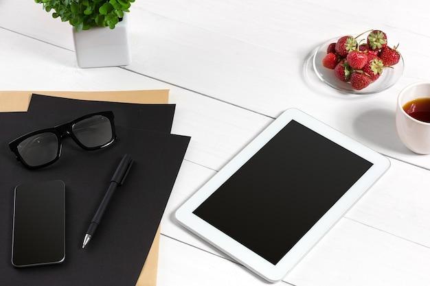 Современное рабочее место с цифровым планшетным компьютером и мобильным телефоном, чашкой кофе, ручкой и пустым листом бумаги. вид сверху и место для копирования текста