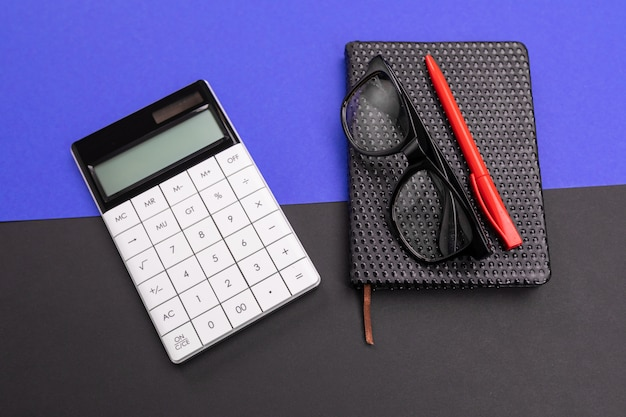 Modern workplace with notebook, pen and calculator isolated on blue black