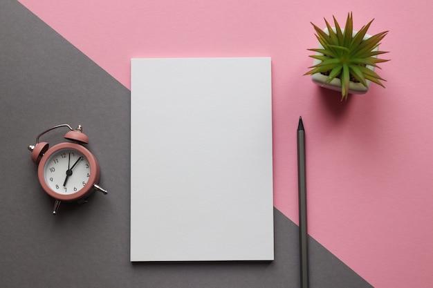 메모장, 연필, 식물 및 알람 시계가있는 현대적인 직장 프리미엄 사진