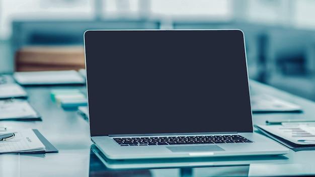 Современное рабочее место с открытым ноутбуком и финансовыми документами, подготовленными для встречи с деловыми партнерами. фотография - это пустое место для вашего текста