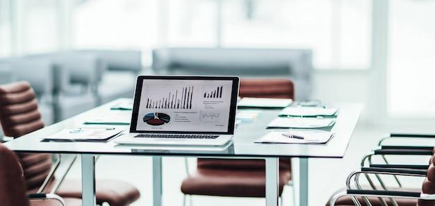 Современное рабочее место с открытым ноутбуком и финансовыми документами
