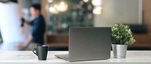 コーヒーカップと植物とオフィスの机の上に置かれたオープンラップトップのモダンな職場
