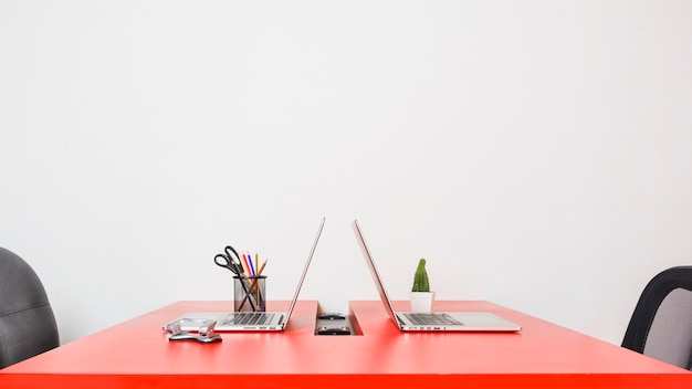 Modern workplace with two laptops on red table against white wall