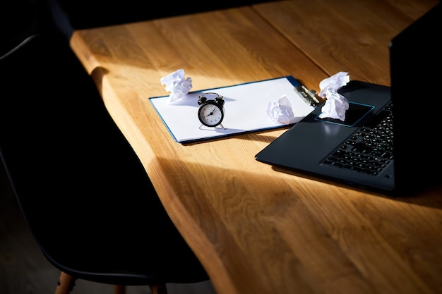 Modern workplace, wooden office desk in hardlight, sunligt with clock, sheet of paper, laptop, notebook, crumpled paper balls, change your mindset, plan b, time to set new goals, business